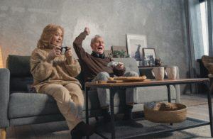 Femme et homme agés heureux qui jouent aux jeux vidéos